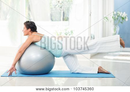 Full length of smiling pregnant woman exercising with ball on mat at fitness studio