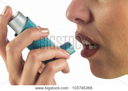 Close-up of woman face while using asthma inhaler against white background