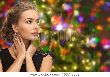 people, holidays and glamour concept - beautiful woman wearing earrings over christmas lights background