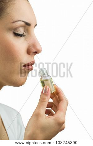 Close-up of female patient with eyes closed while smelling bottle of medicine against white background