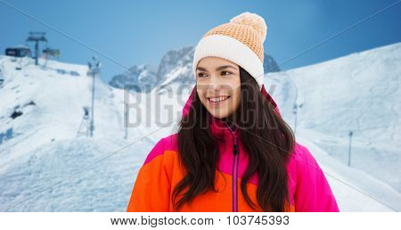 winter, leisure, clothing and people concept - happy young woman or teenage girl in winter clothes over downhill skiing and mountains background