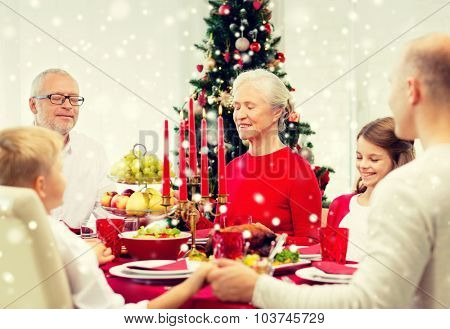 family, holidays, generation, christmas and people concept - smiling family having dinner and praying at home