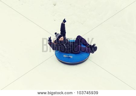 winter, leisure, sport, and people concept - happy teenage boy or young man sliding down on snow tube and showing victory gesture