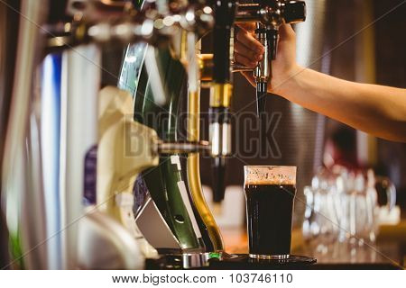 Cropped hand of bartender dispensing beer at bar counter