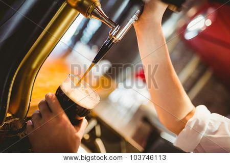 Cropped hand of barkeeper dispensing beer at bar counter