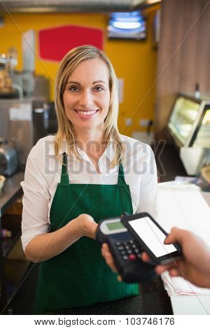 Portrairt of female worker accepting payment from customer through NFC in bakery