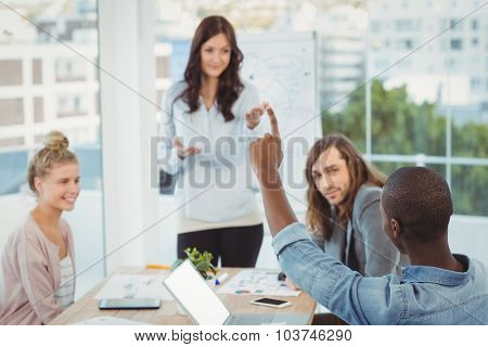 Man with hand raised while discussing with coworkers at creative office