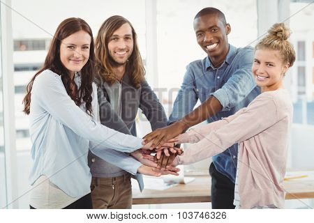 Portrait of smiling business team putting their hands together at office