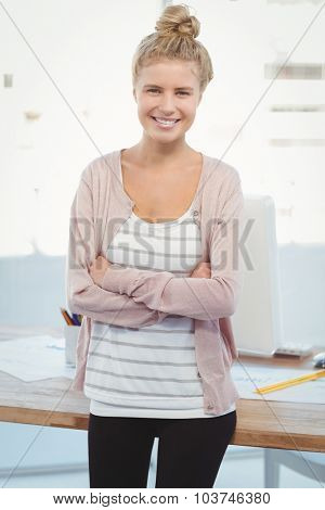 Portrait of happy woman with arms crossed while standing in office