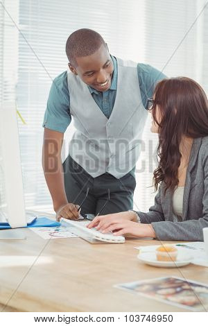 Smiling businessman discussing with coworker at desk in office