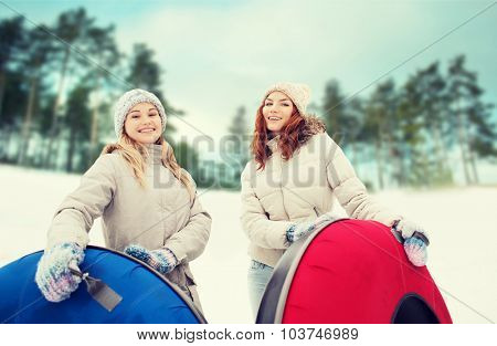 winter, leisure, sport, friendship and people concept - happy girl friends with snow tubes outdoors