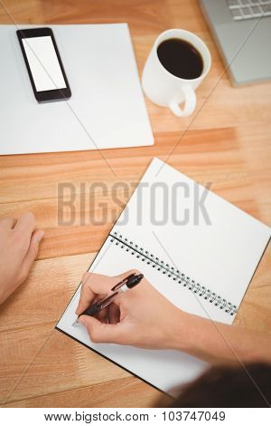 Cropped hand of man writing on spiral notebook at desk in office
