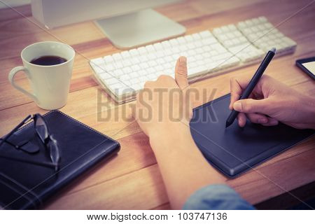 Cropped image of hipster using graphics tablet on desk in office