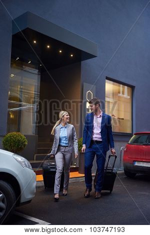 Young business people couple entering city  hotel, looking for room, holding suitcases while walking on street
