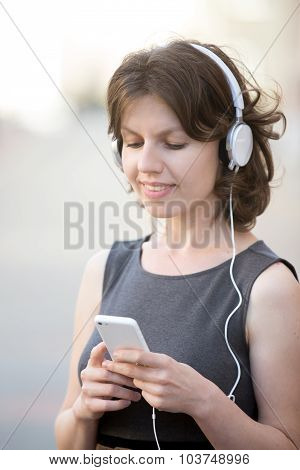 Smiling Female Choosing Song On Device