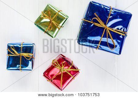 Shiny  Gift Boxes On White Wood Background