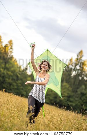 Happy Young Woman Running Through A High Golden Grass Flying A Kite