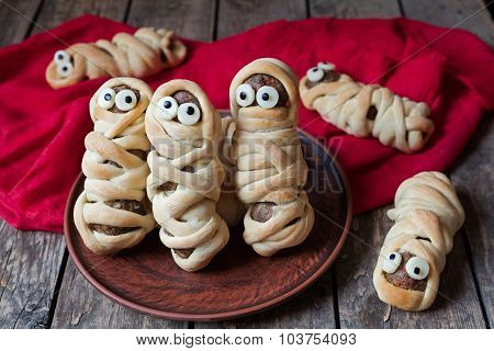 Scary halloween food meatball sausage mummies wrapped in dough with eyes  on vintage wooden backgrou