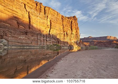 Colorado River at sunrise in Canyonlands National Park with rock cliffs and sandbar