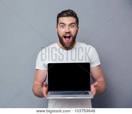 Portrait of a cheerful man showing blank laptop computer screen over gray background