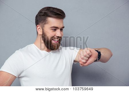 Portrait of a smiling man looking on wrist watch over gray background