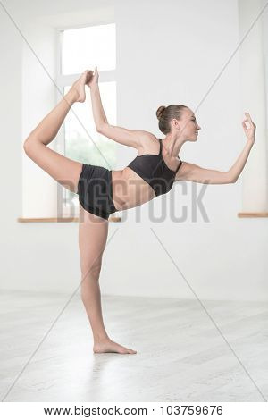 Full length portrait of a beautiful woman doing stretching exercises in gym