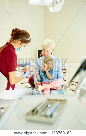 Pediatric dentist explaining to young patient and her mother