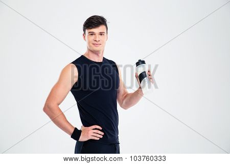Portrait of a happy sports man holding bottle with water isolated on a white background