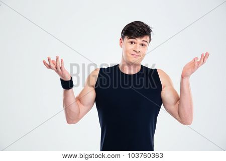 Portrait of a fitness man shrugging shoulders isolated on a white background