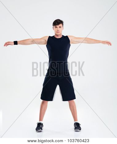 Full length portrait of a fitness man doing warm up exercises isolated on a white background