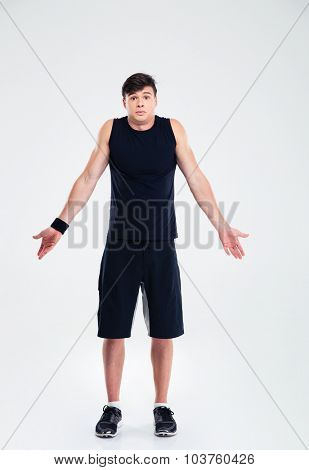 Full length portrait of a sports man shrugging shoulder isolated on a white background