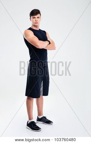 Full length portrait of a serious fitness man standing with arms folded isolated on a white background and looking at camera