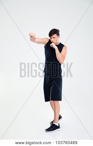 Full length portrait of a handsome man boxing isolated on a white background