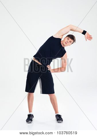 Full length portrait of a fitness man doing stretching exercises isolated on a white background