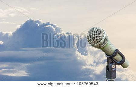 Microphone On A Stand With Blurred Gray Big Cloud Before Raining In Twilight, Copyspace On The Left.