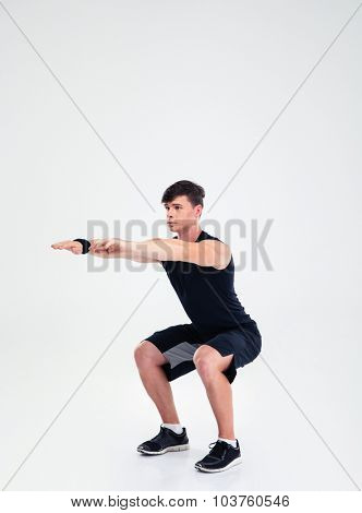Full length portrait of a fitness man doing squatting exercises isolated on a white background
