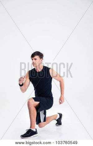 Full length portrait of a sports man warming up isolated on a white background