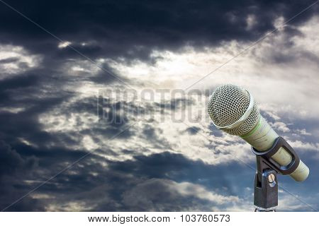 Microphone On A Stand With Blurred Dark Gray Big Cloud Before Raining In The Evening, Copyspace On T