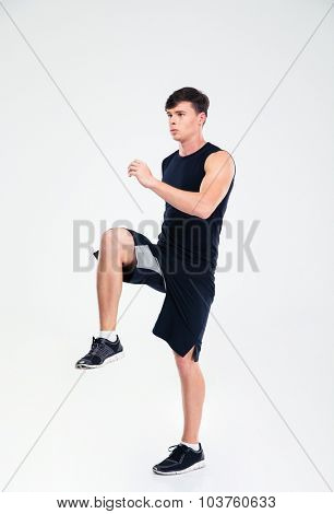 Full length portrait of athletic man warming up isolated on a white background