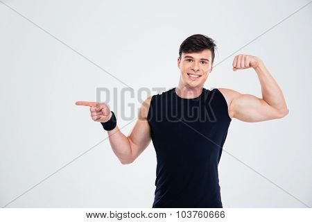 Portrait of a happy man showing his biceps and pointing finger at copyspace isolated on a white background
