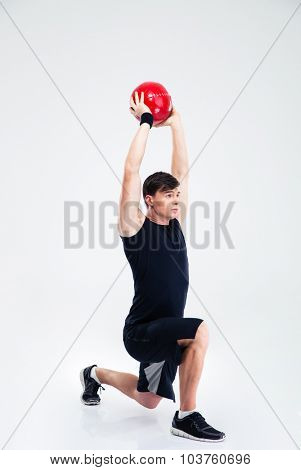 Full length portrait of athletic man workout with fitness ball isolated on a white background