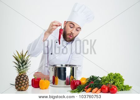 Portrait of a young chef cook preparing soup isolated on a white background