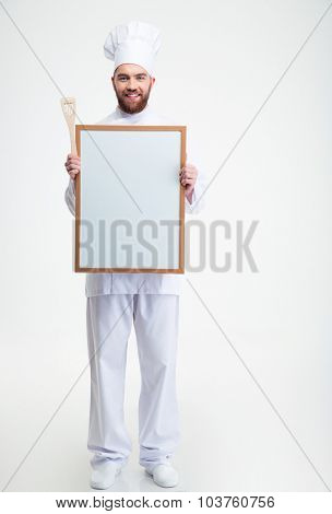 Full length portrait of a cheerful male chef cook iun uniform holding blank board isolated on a white background
