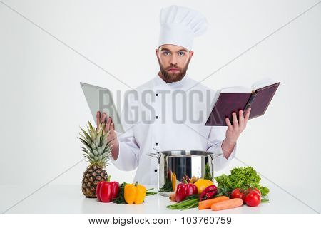 Portrait of a handsome male chef cook holding table computer and recipe book while preparing food and looking at camera