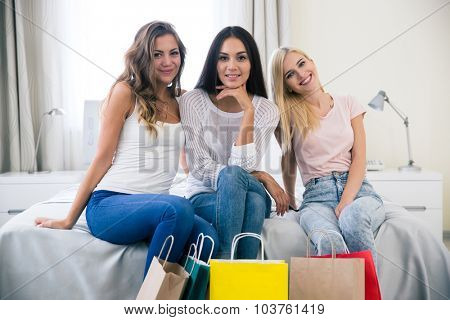 Portrait of smiling three girlfriends with shopping bags at home