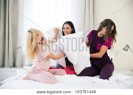 Portrait of a funny girlfriends fighting with pillows on the bed at home