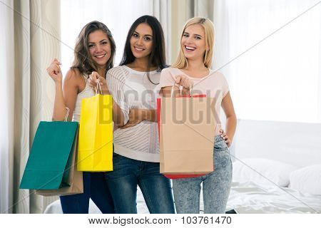 Portrait of a cheerful three girls with many shopping bags at home