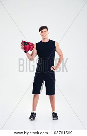Full length portrait of a fitness man holding boing gloves isolated on a white background and looking at camera