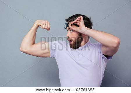 Portrait of a man looking at his biceps with delight over gray background