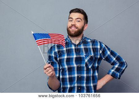 Portrait of a smiling man holding USA flag over gray background